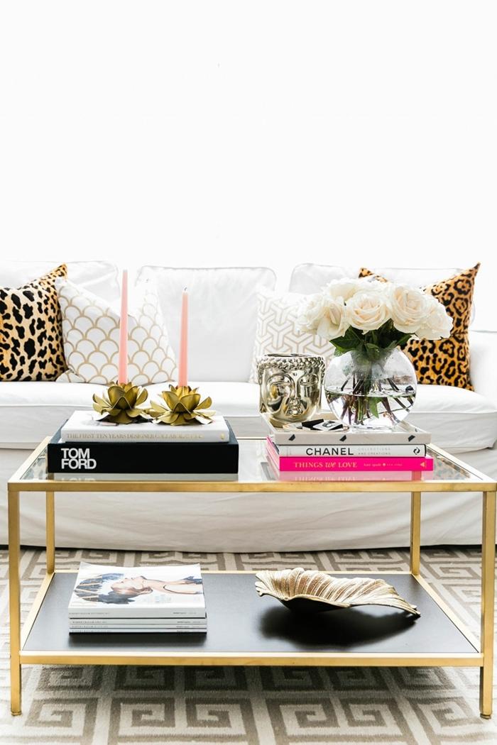 table de salon encadrement doré, livres en rose, blanc et noir, coquille, coussins déco, tapis motifs géométriques