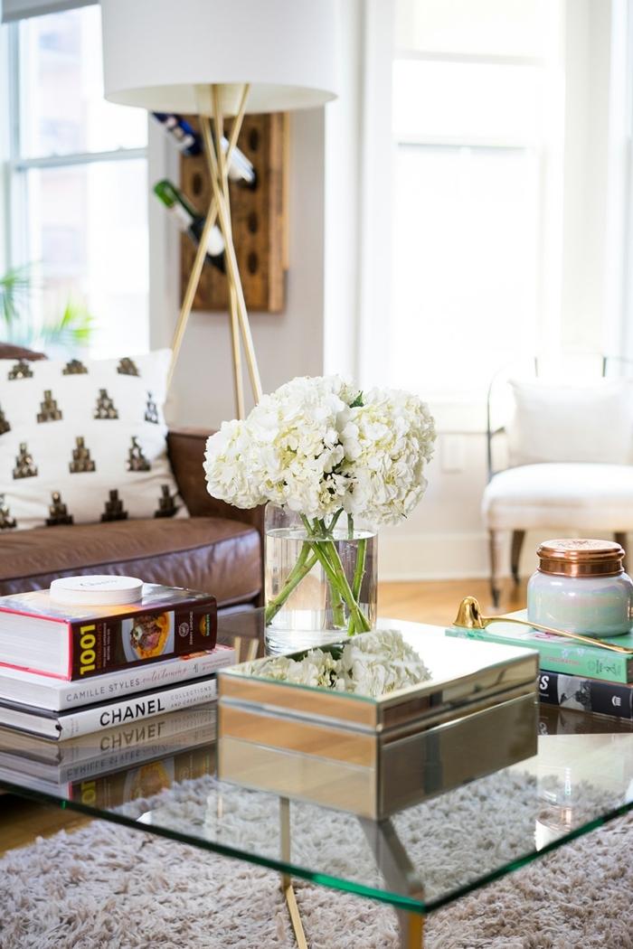 lampe tripode, vase pleine d'hortensias blanches, chaise blanche, boîte en bois et verre, livres empilés