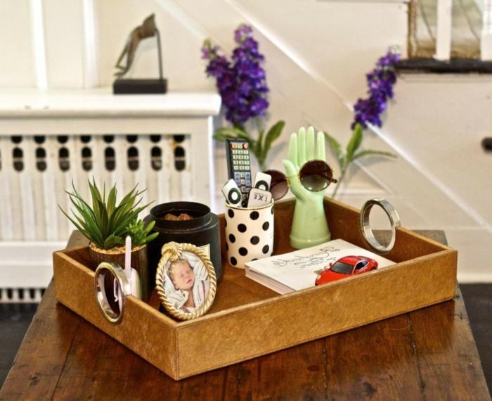 plateau de bois et objets accumulés, petite photo de bébé avec encadrement rond, pot de fleur, tasse pointillé, sculpture avant-garde