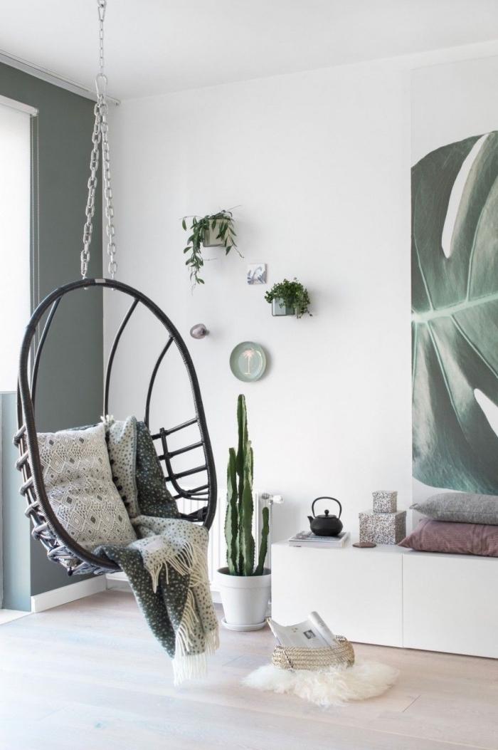 deco salon scandinave et bohème chic en blanc et vert avec un fauteuil cocooning suspendu au plafond et quelques accents verts