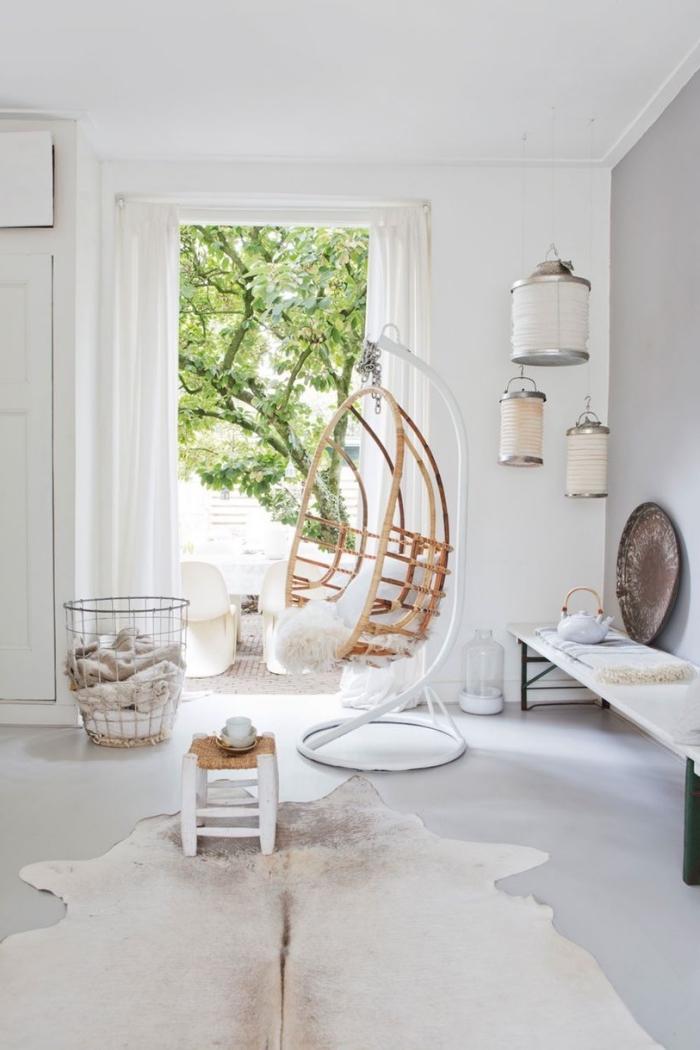 salon blanc immaculé aux accents déco ethnique chic avec un fauteuil suspendue accessoirisé avec un peau de mouton scandinave pour une ambiance cosy et relaxante