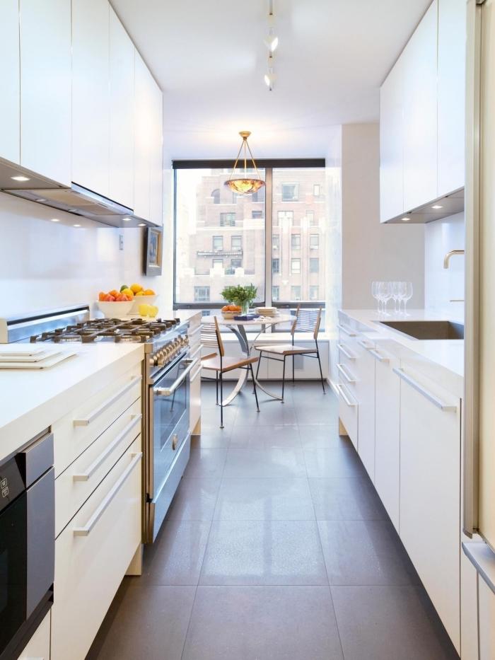 agencement de cuisine avec unités face à face, modèle de cuisine moderne en blanc avec robinet inox et carrelage sol gris