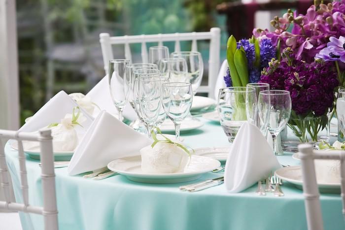 décoration élégante de mariage avec des serviettes blanches pliés en triangles sur nappe bleu clair, verres à vin, composition florale en fleurs mauve et violettes