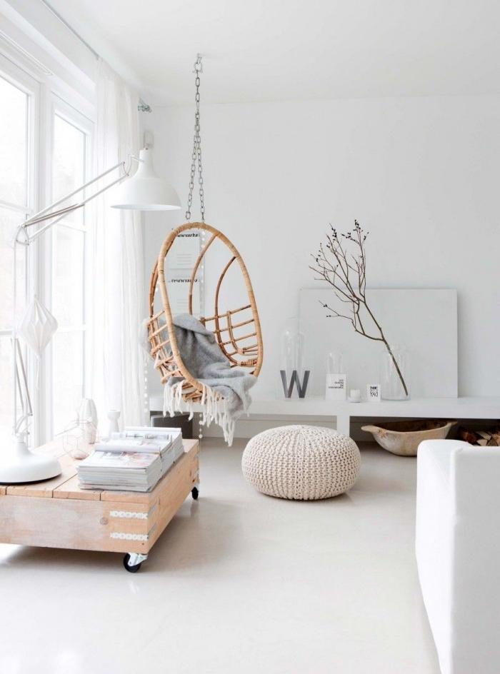 intérieur blanc cocooning dans un salon de style scandinave épuré avec une balançoire d'intérieur en rotin et un pouf tricoté