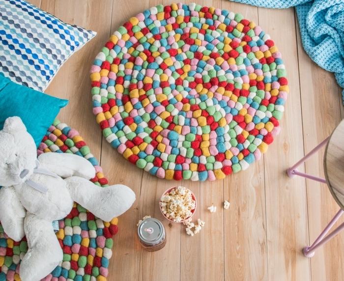 faire un tapis de jeu enfant multicolore, modèle de tapis en pompon mini, idée déco chambre d'enfant avec objets personnalisés