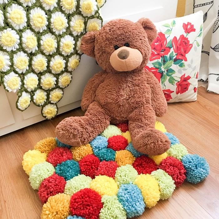 idée pour réaliser un tapis de jeu enfant multicolore, modèle de tapis en pompon diy pour la chambre d'enfant
