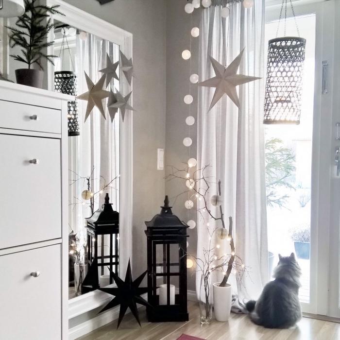 deco salon gris et blanc dans l'esprit de fête, coin du salon décoré de lanternes déco, d'étoiles en papier suspendues et d'une jolie guirlande de boules lumineuses