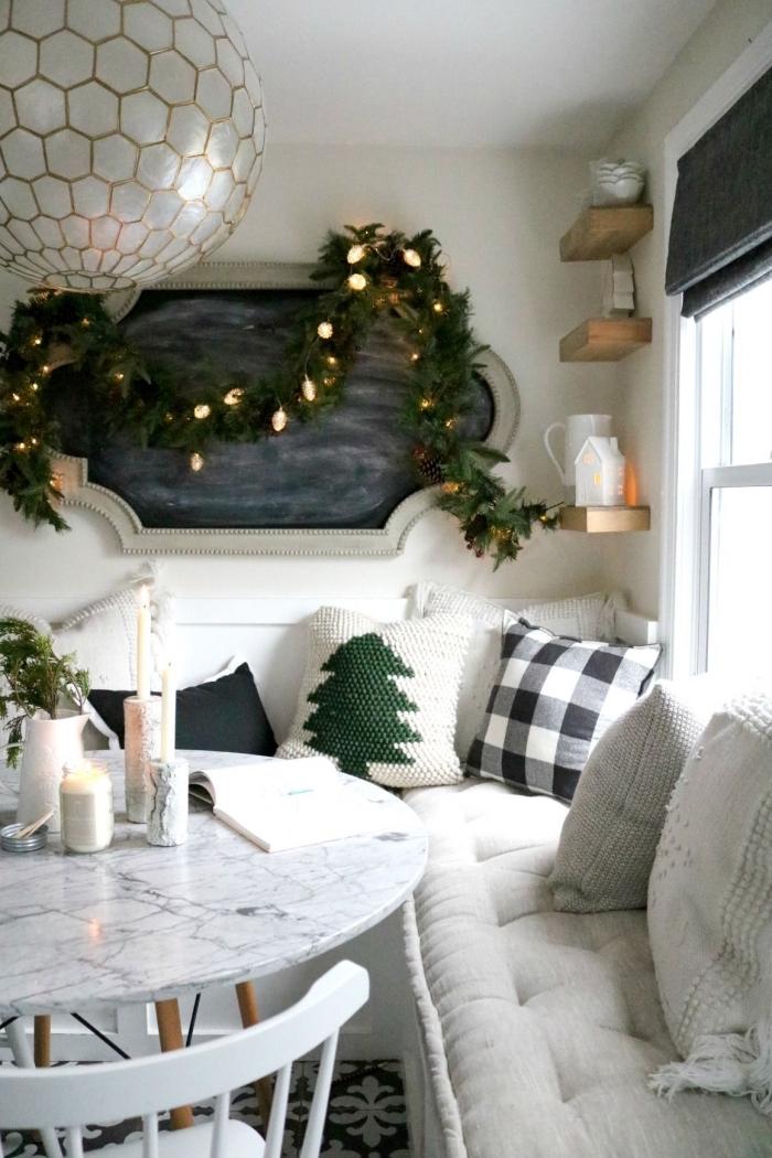 deco sejour dans l'esprit de fête scandinave traditionnel, coin repas d'angle avec table ronde en bois et marbre décorée de bougies et d'un vase en céramique, coussin cocooning tricoté à motif sapin de noël