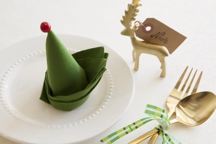 idée pour pliage de serviette en tissu vert, décoration de table de Noel avec une figurine dorée en forme de cerf