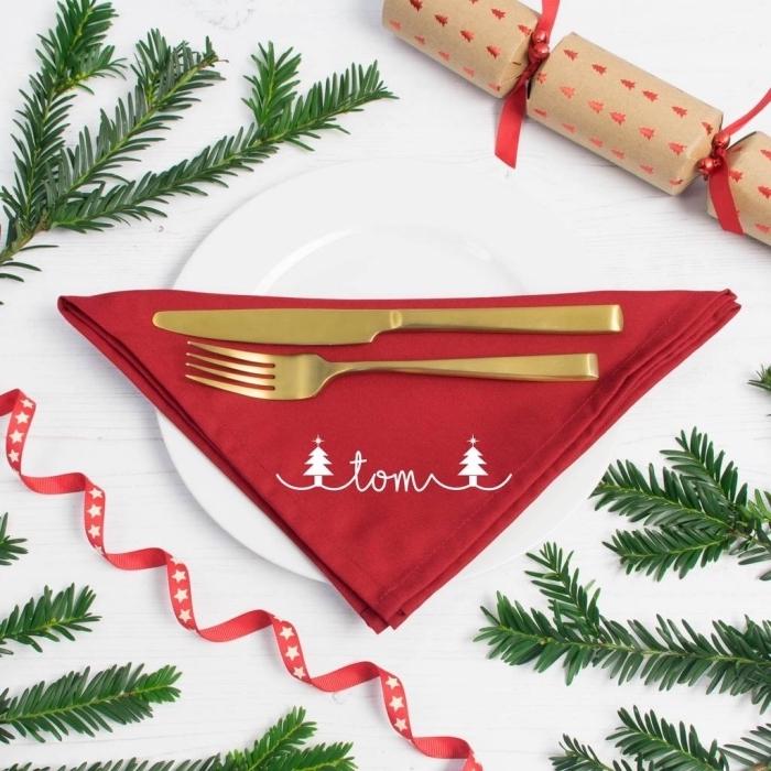 modèle de serviette en tissu rouge avec petit symbol noel et vaisselle en or, idée déco de table noel en blanc et rouge