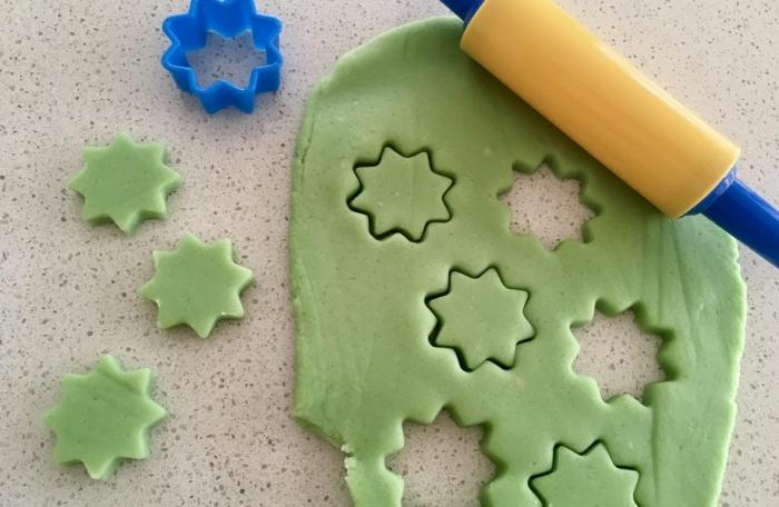 pâte à modeler faite maison étalée sur un plan de travail avec un mini-rouleau à pâtisserie, étoiles découpées dans la pâte à l'aide d'un emporte-pièce