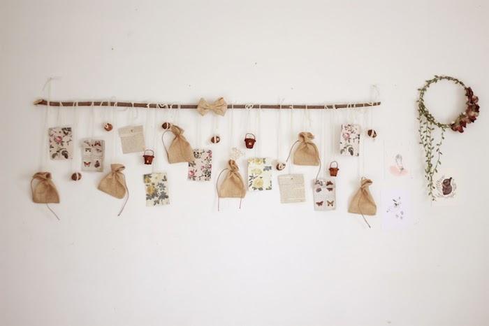 branche de bois flotté sur mur blanc avec petits sachets cadeau et différentes décorations vintage chic, couronne de noel fleurs séchées, calendrier de l avent a faire soi meme