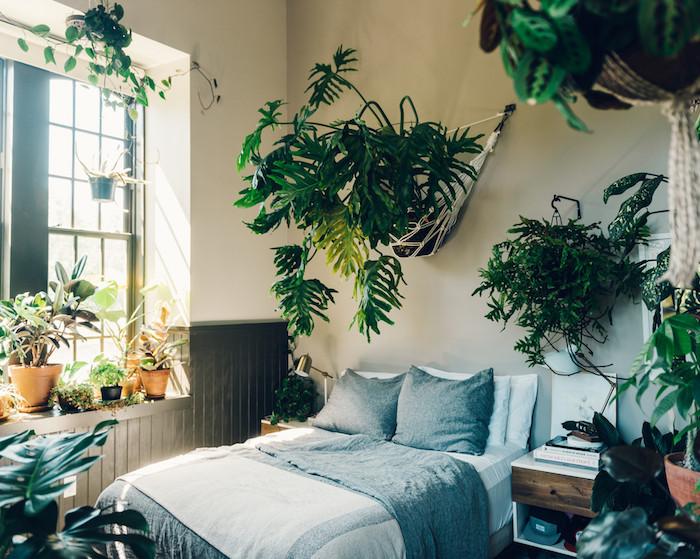 deco tropicale chambre style tumblr avec de la végétation verte partout, plantes vertes au rebrod de fenêtre et pots de plantes suspendus au mur avec macramé, linge de lit gris et blanc
