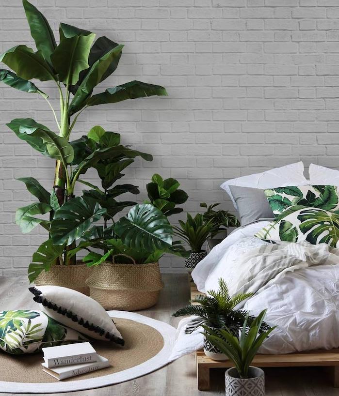 matelas sur palettes de bois, bananier et monstera dans un panier, tapis rond, coussins à motif exotique monstera, mur de briques blanches