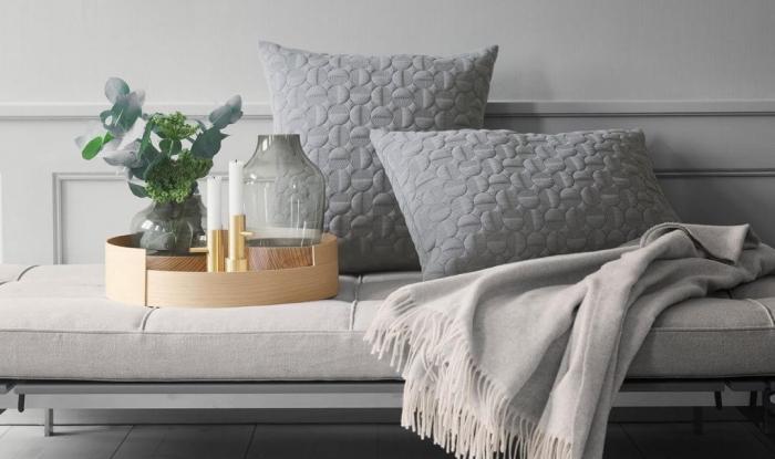 les accessoires indispensables pour un salon hygge deco scandinave, coussins gris à motifs texturés, une couverture douillette et un joli plateau déco en bois avec un petit vase en céramique