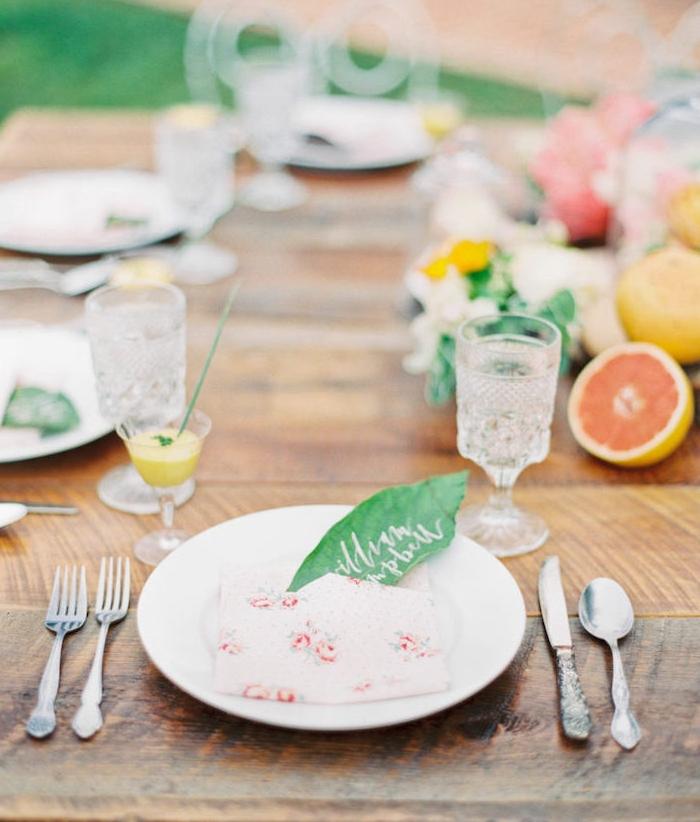 idee de table style champetre chic mariage avec centre de table en fleurs et fruits frais, serviette pliée avec poche et marque place en feuille verte avec nom invité sur table bois brut