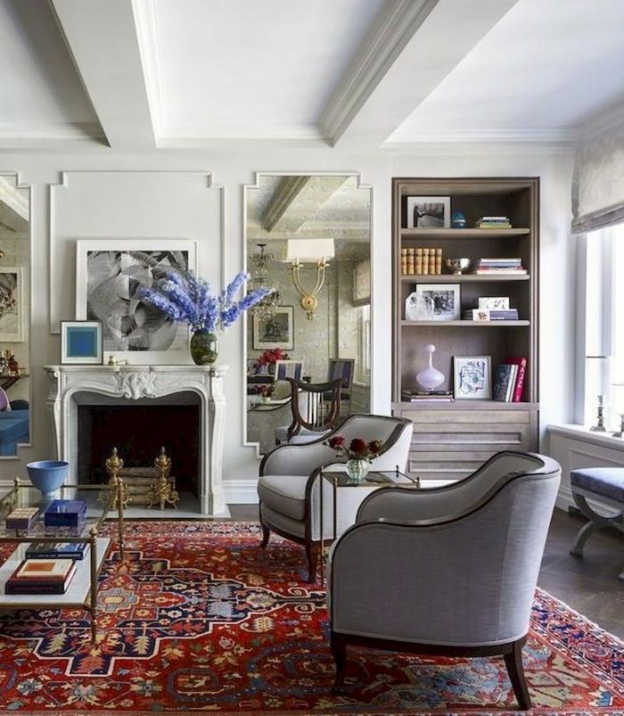 salon cosy et élégant aux meubles vintage, déco campagne esprit brocante, cheminée blanche, tapis persan, deux fauteuils gris