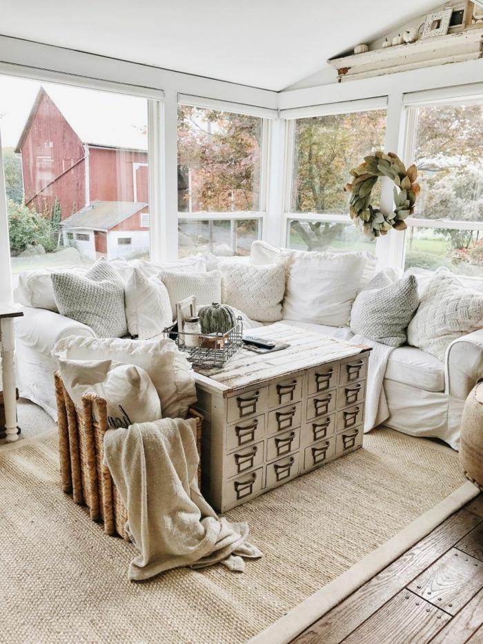 table au rangement apothicaire, coussins blancs et gris, grand panier rustique, grandes fenêtres, tapis fibre naturel, déco campagne esprit brocante