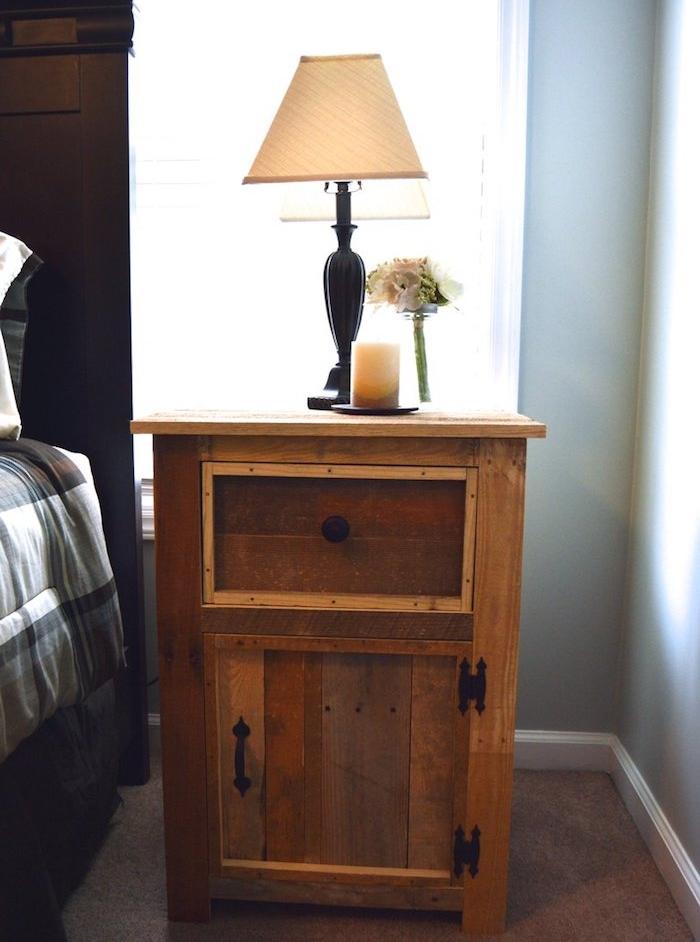 table basse infustrielle vintage en planches de bois de palette décomposée, lampe de nuit vintage, bougies, bouquet de fleurs blanches