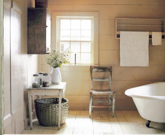 déco salle de bain rétro avec meubles anciens en bois rustique sur sol parquet et baignoire ancienne