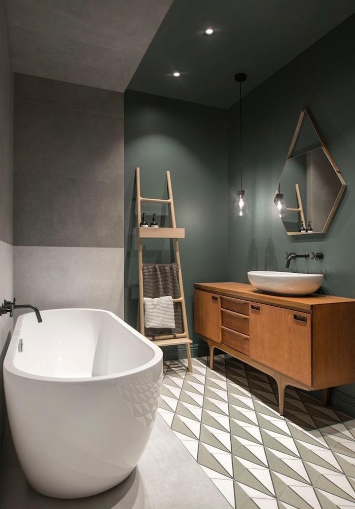 salle de bain scandinave avec meuble lavabo en bois retro sol en carrelage et ciment et murs bicolores vert de gris kaki et béton ciré avec baignoire design