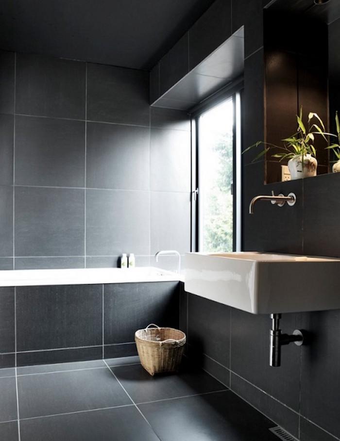 salle de bain avec carrelage gris anthracite sombre sur sol et murs avec lavabo carré suspendu