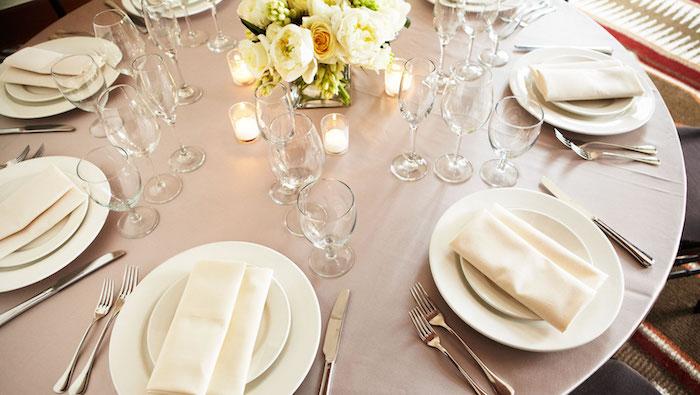 comment plier une serviette en tissu en forme de pochette blanche dans assiettes blanches sur nappe couleur cappuccino, centre de table en fleurs jaunes et blanches