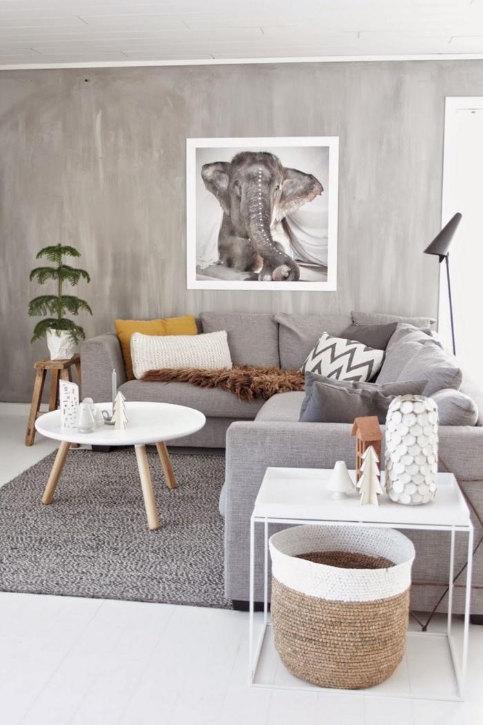 deco salon gris de style scandinave moderne avec un grand canapé d'angle gris recouvert de coussins décoratifs couleur uni ou à motifs géométriques et des accents déco de bois naturel, mur gris effet ciment sublimé par un poster photo grand format