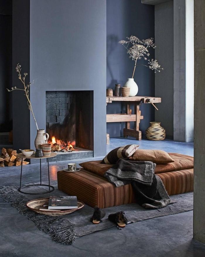 déco salon cocooning de charme rustique et authentique avec une cheminée ouverte et un petit coin de détente autour d'un matelas de sol