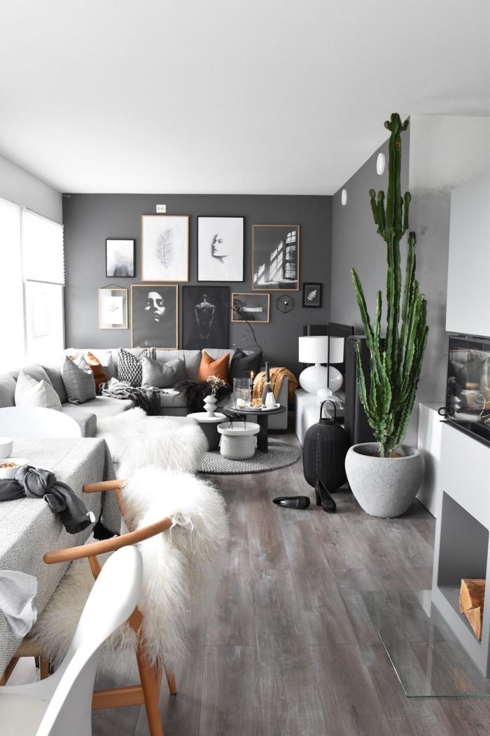deco salon scandinave moderne ouvert sur la salle à manger, avec une galerie murale de cadres photos élégants sur un fond gris foncé
