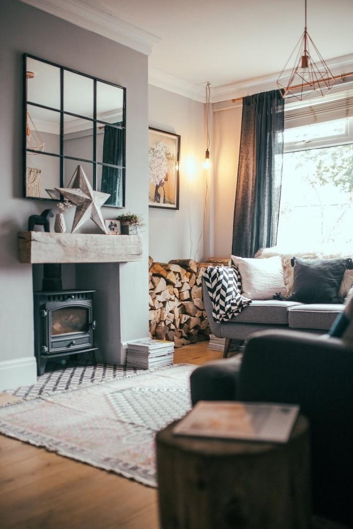 ambiance chaleureuse et accueillante dans un salon aux accents rustiques, coin cheminée décoré avec un grand miroir à carreaux et un range-bûches à côté