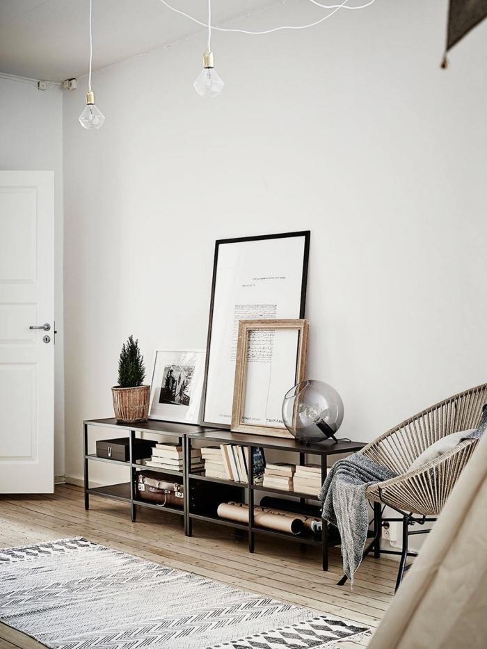 ambiance hygge dans un salon scandinave avec un tapis cocooning à motifs ethniques, une chaise acapulco et des posters photos personnalisés