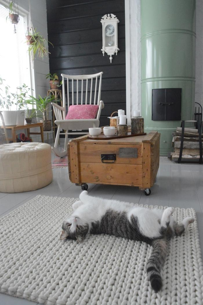 coin cheminée d'esprit hygge deco avec une table basse en bois récup, une chaise basculante et un pouf en cuir, un chat mignon allongé sur un tapis tricoté gris devant la cheminée