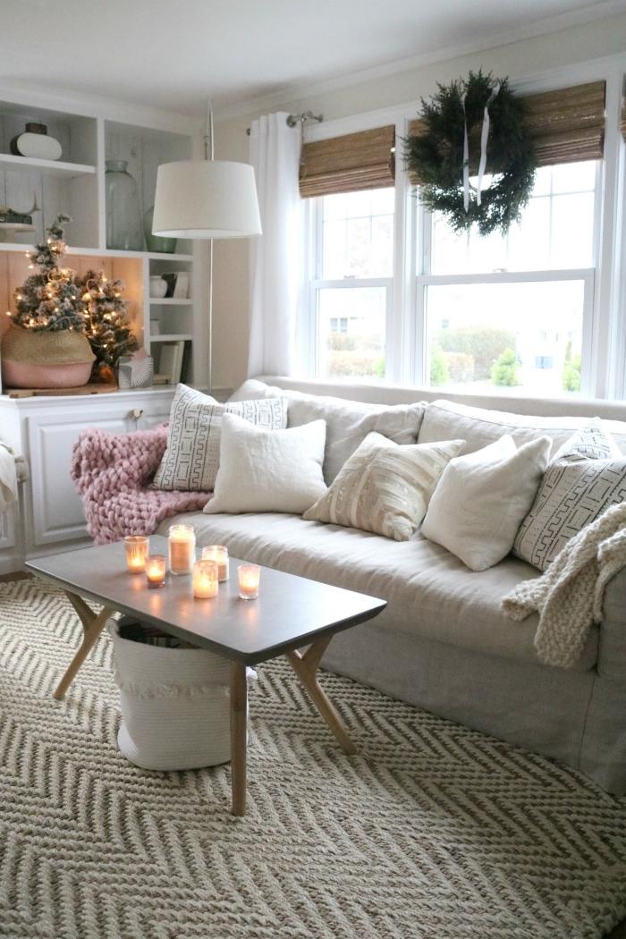 deco sejou cocooning dans un esprit de fête scandinave et traditionnel avec un canapé moelleux agrémenté de coussins, une déco de table basse de bougies et un joli sapin de noël dans un panier