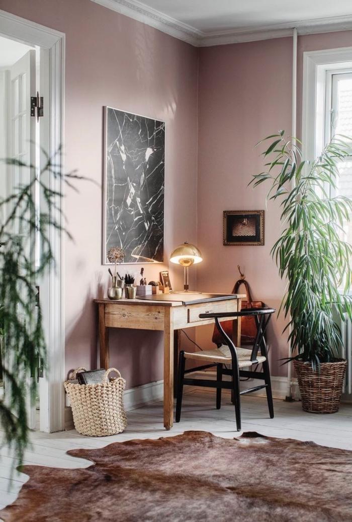un coin bureau en bois et noir aménagé dans un salon rose poudré cocooning au sol boisé blanc, tapis de peau de bête pour un accent authentique dans le salon