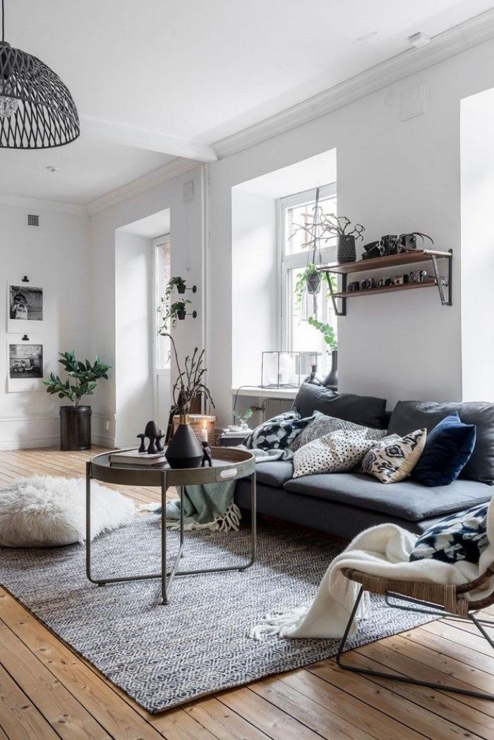coussin cocooning en fausse fourrure blanche jeté au sol sur un canapé tissé gris, en contraste avec le parquet en bois du salon vintage scandinave