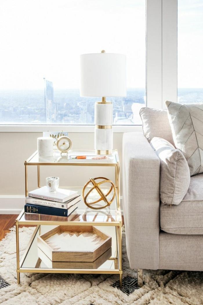 table basse à deux niveaux, encadrement doré, plateau en bois hexagonal, livres, lampe blanche