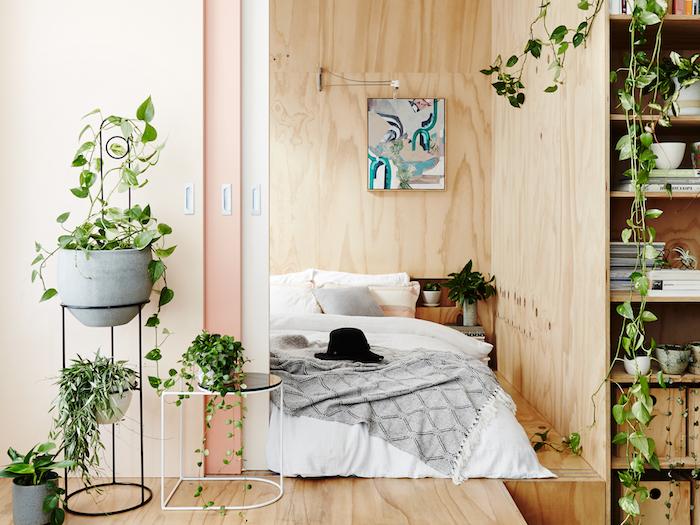 revêtement sol et mur bois, matelas au sol avec linge de lit gris et blanc, plante tombante intérieur, bibliothèque avec plantes et livres