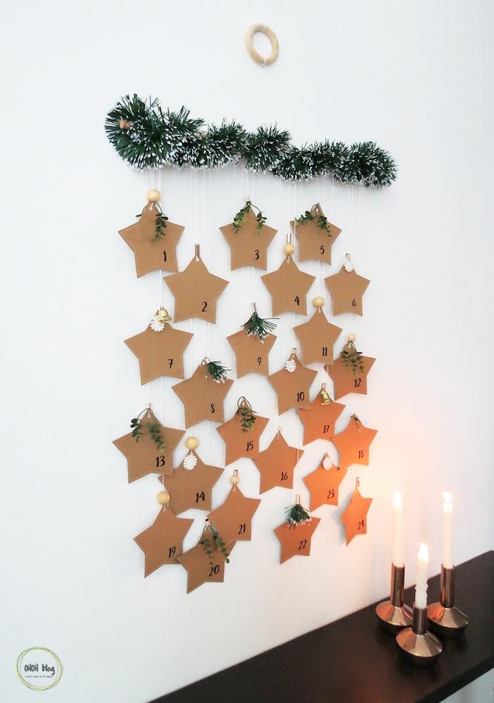 calendrier de l avent en branche de pin artificielle avec des étoiles en papier kraft suspendues comme deco murale de noel