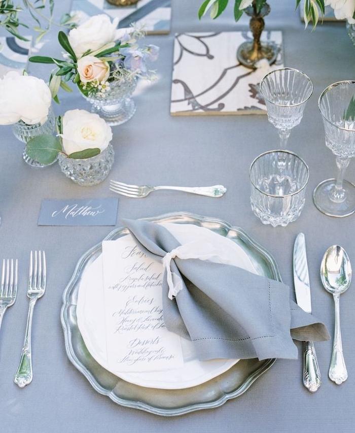 table revêtue de nappe grise avec de petits bouquets de fleurs, couverts argent et vaisselle vintage, deco mariage champetre