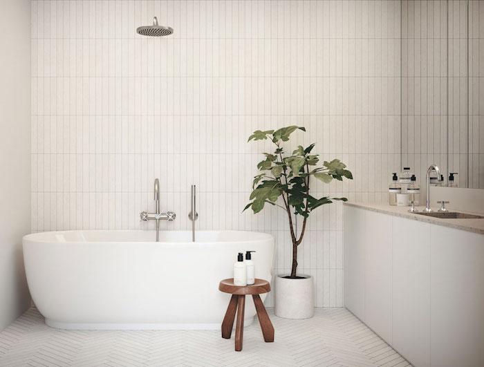 salle de bain stye scandinave avec carrelage blanc sur le sol et murs et baignoire ilot ovale avec tabouret en bois et plante verte