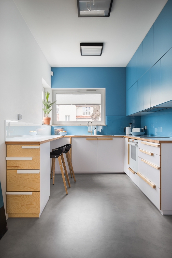 photo cuisine moderne avec mur en couleur, exemple de petite cuisine aménagée en forme U avec meubles haut en bleu