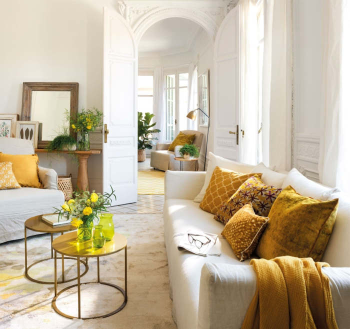 grand sofa gris clair, tables basses, coussins moutarde, miroir encadré, peinture murale blanche, salle de séjour
