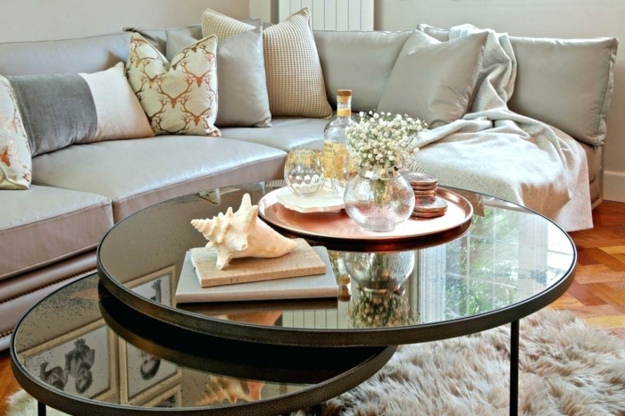 tables gigognes rondes, tapis poilu, coussins neutres, plateau cuivré avec vases, livres et coquillage, sofa d'angle gris