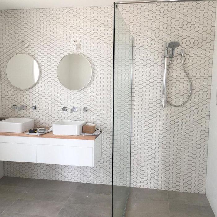 salle de bain ouverte sur sol en béton ciré et douche italienne avec cloison en verre et double vasque et miroirs ronds