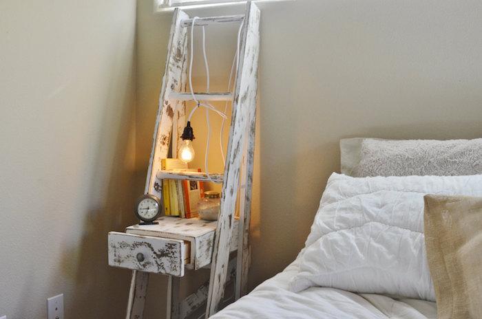echelle decorative recyclée en bois patiné blanchi avec tiroir, ranger livres, réveil, lampe ampoule, linge de lit blanc