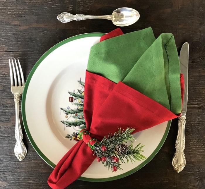 idée pliage de serviette en tissu bicolore avec rond à serviette diy ruban rouge et branches de sapin, déco de table fête