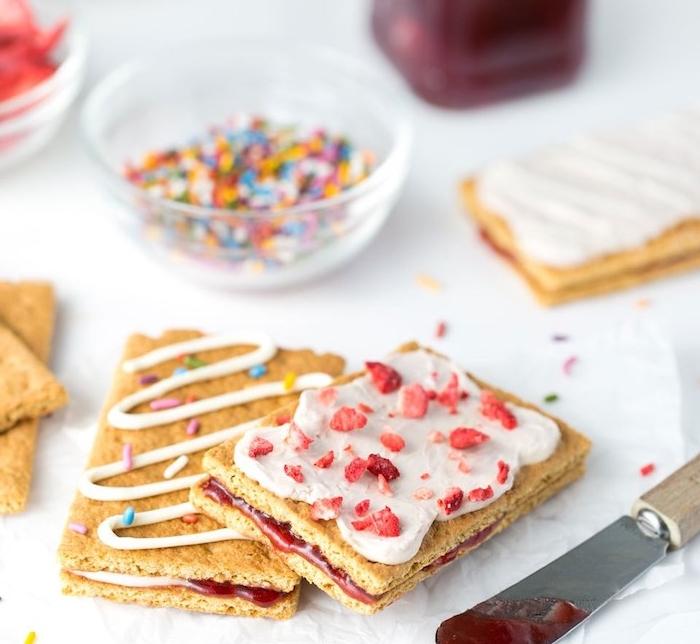 biscuits sucrés avec fromage à la crème, confiture fraise maison et topping de vermicelles arc-en-ciel et bonbons