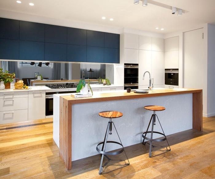 déco de cuisine moderne aux meubles blancs avec armoires haut cuisine en bleu canard, exemple de cuisine avec îlot blanc et bois