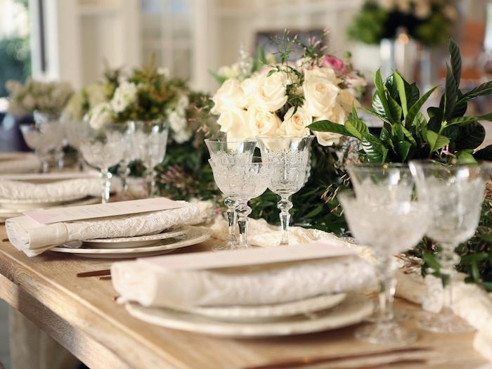 composition florale de mariage en guise de centre table et chemin de table dentelle blanche, pliage simple en rectangle dentelle sur table bois rustique